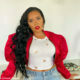 Angela Simmons pairs denim jeans with red, puff-sleeved jacket