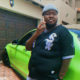 Heavy K poses in grey and black outfit against neon green car