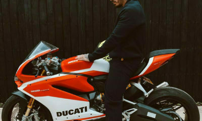 J Balvin poses against red Ducati bike