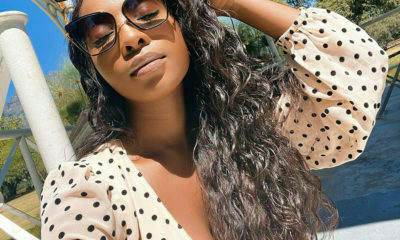 Pearl Modiadie poses while showing off brown, wavy hair