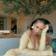 Thuli Phongolo wears beige, figure-hugging dress at a scenic location