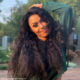 Simphiwe Ngema poses in long, curly wig and shimmery eyeshadow