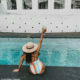 Linda Mtoba poses poolside in spaghetti-strapped swimsuit and straw hat
